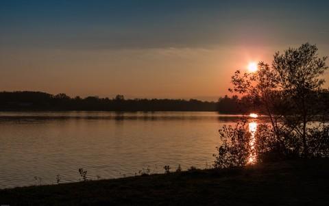 Coucher de soleil sur le Lac de Miribel (Ain) Par une belle journée d'automne, quelques photosdu soleil qui disparaît derrière les arbres pour plonger dans la ville de Lyon lointaine